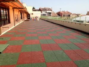 Terraza de guarderia ejecutada con pavimento en losetas de caucho de exterio para zonas de juegos infantiles